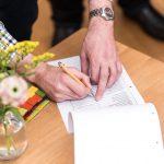 Die Mitglieder unterschreiben die Teilnehmerliste