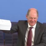 Olaf Scholz zeigt bei der Pressekonferenz einen Stapel mit den beschlossenen Gesetzen, Screenshot