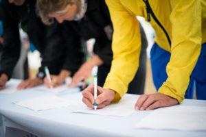 Mehrere Menschen stehen vornübergebeugt und zeichnen eine Petition mit