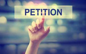 """Ein Finger bedeutet auf ein Schild mit der Beschriftung """"Petition"""""""